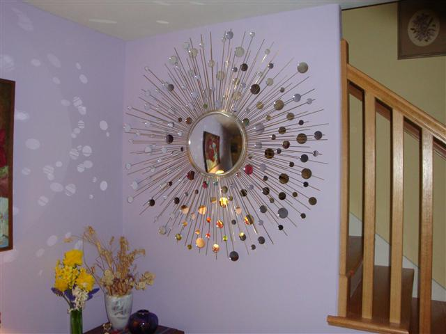 the convex center mirror is surrounded by three sizes of satellite mirrors mounted on solid brass rays
